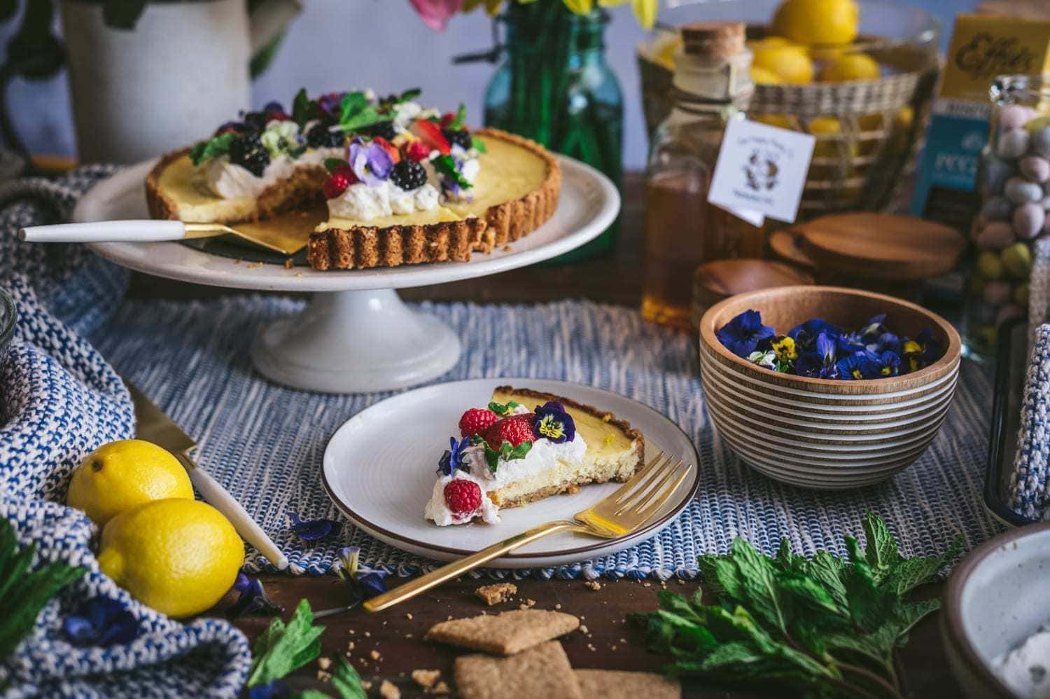 lemon honey ricotta pie qith whipped cream, berries and edible flowers with slice cut out