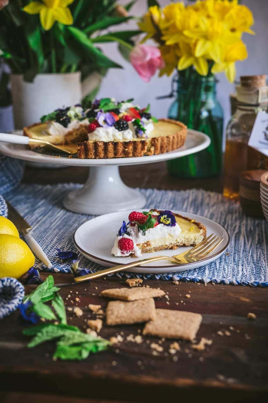 slice of lemon honey ricotta pie qith whipped cream, berries and edible flowers