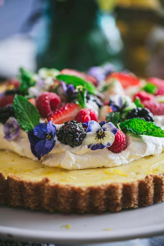 lemon honey ricotta pie qith whipped cream, berries and edible flowers